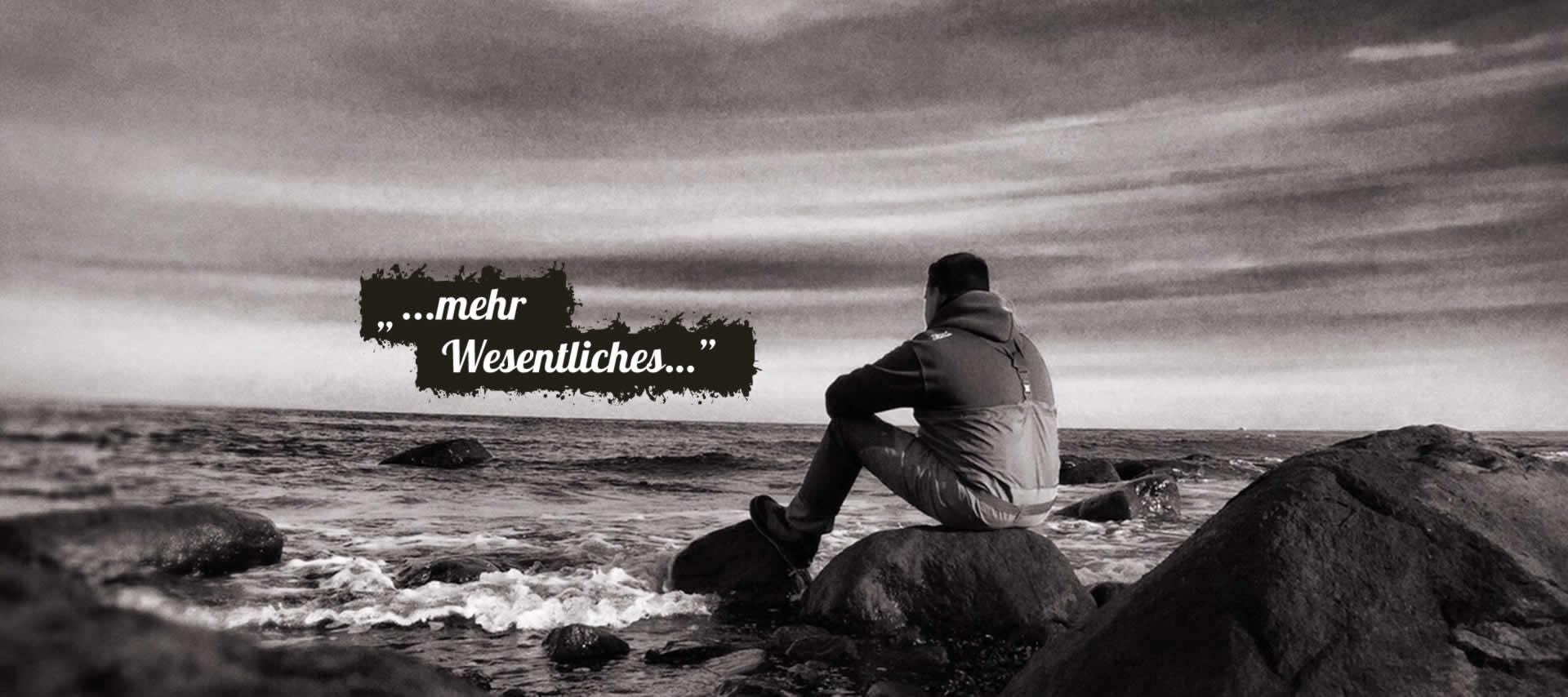 Mann blickt am Meer in die Ferne